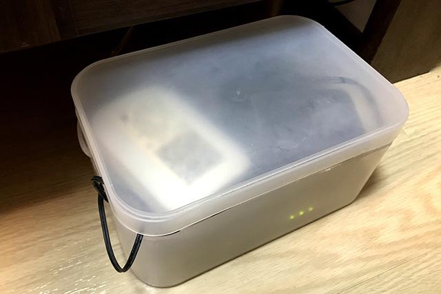 食器棚下のケース内にONUとルーターが重ねおき状態